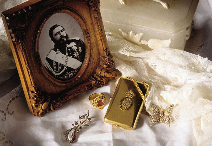 King Kalakaua was the last reigning King of the Hawaiian Kingdom.  Show here is a photo of His Majesty King Kalakaua, his ring, and pieces of jewelry belonging to his wife, Queen Kapiolani, including her diamond broach, compact, and diamond butterfly pin with wings that will flutter gently when moved.  (Hawaii Visitors and Convention Bureau (HVCB)/Linda Ching)