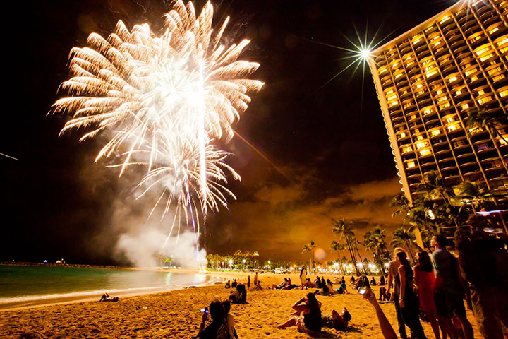 Fireworks light up the night sky and bring revelers out to the beach to celebrate.  Photo courtesy of Hawaii Tourism Authority (HTA) / Tor Johnson.