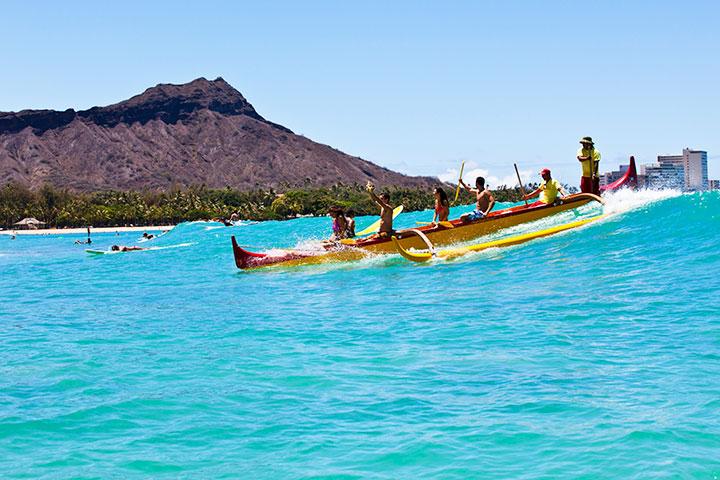 Canoe surfers at Waikiki beach with Diamond Head in the background.  Photo courtesy of Hawaii Tourism Authority (HTA) / Tor Johnson.