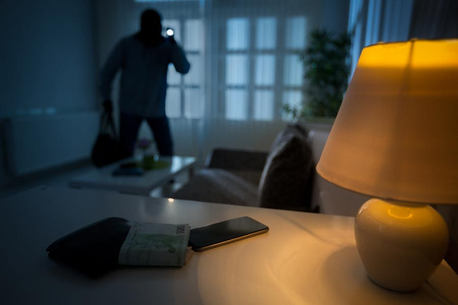 A burglar searches an empty room after breaking in