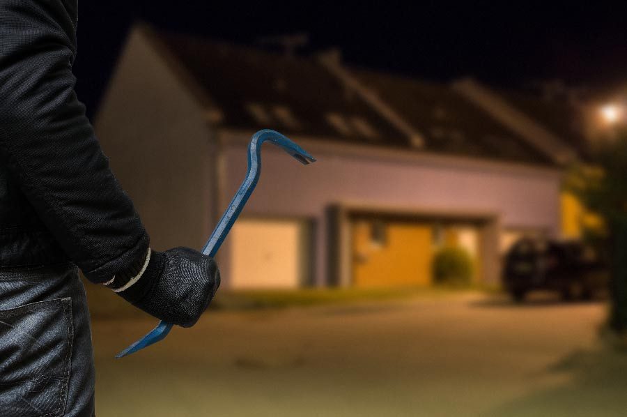 Man with crowbar gets ready to break into a house