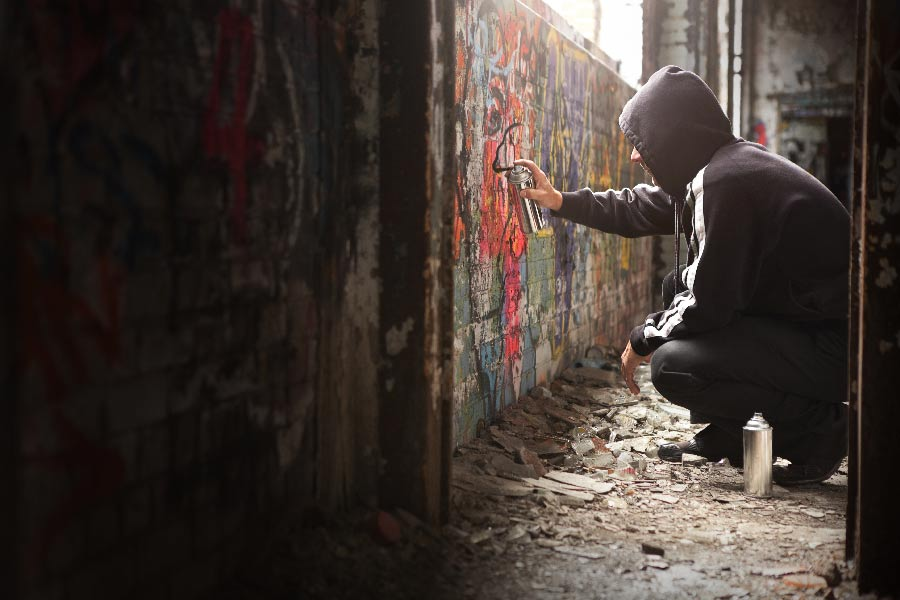 A kid spray painting a wall vandalizes an empty building