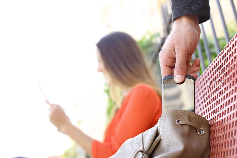 A sneaky person steals a cell phone from a womans purse