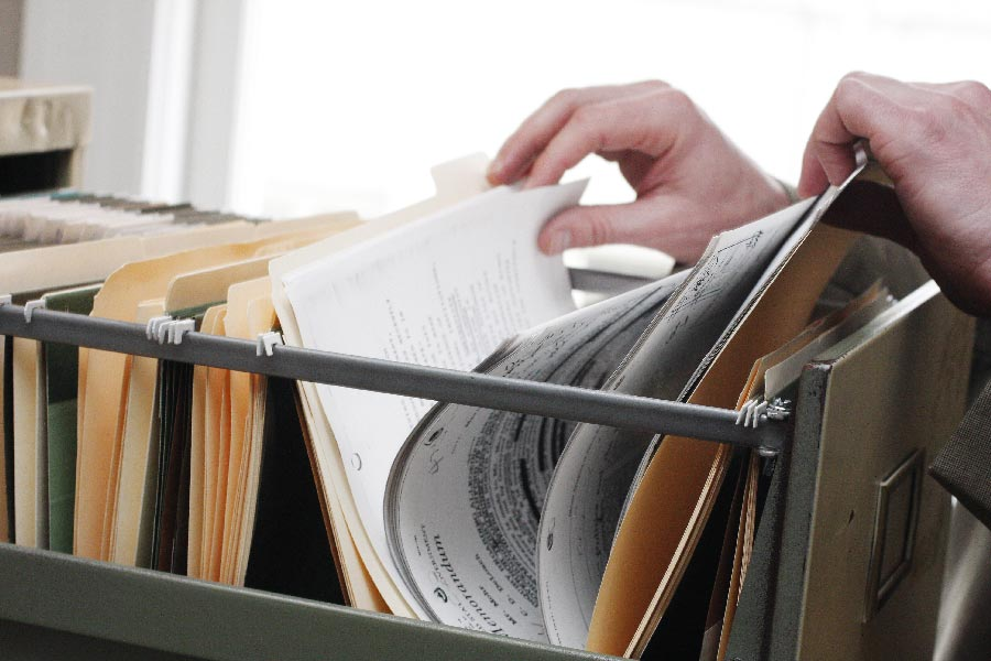 Someone sorts through a file drawer looking for traces of fraud