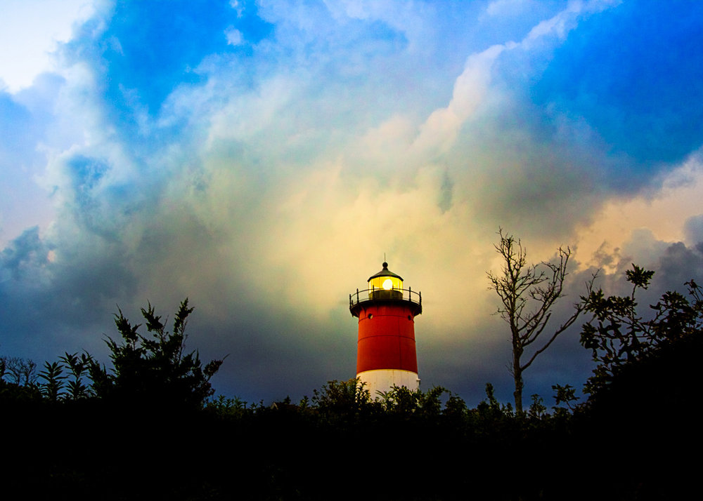 A lighthouse on cape cod rising above the trees.