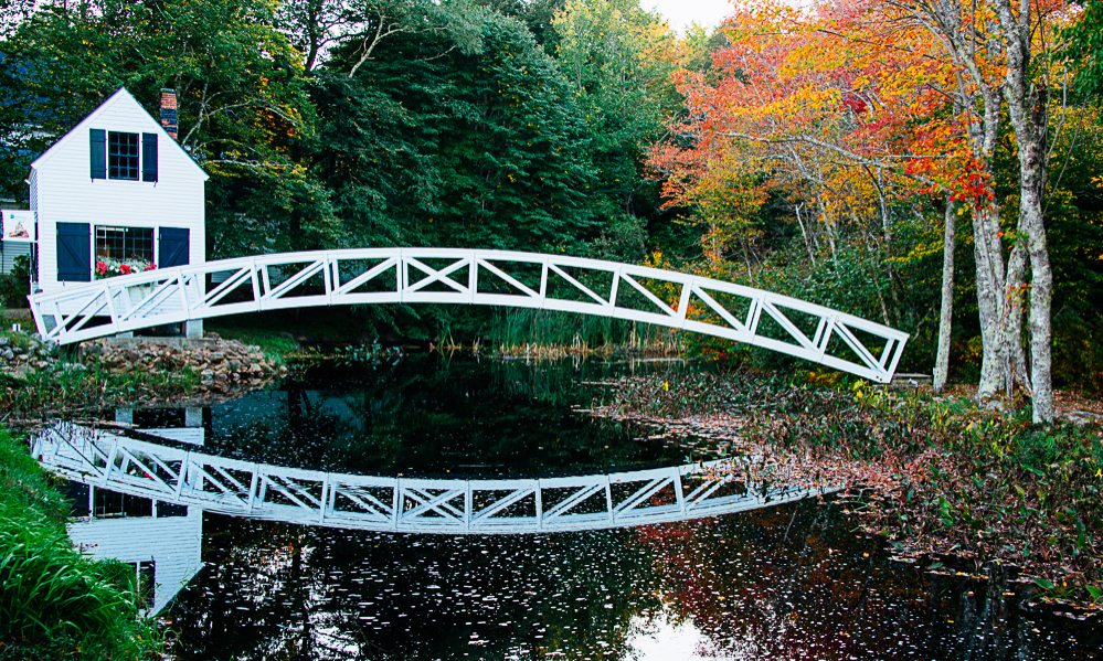 A white bridge and fall foliage over a river near Acadia National Park in Bar Harbor, Maine.