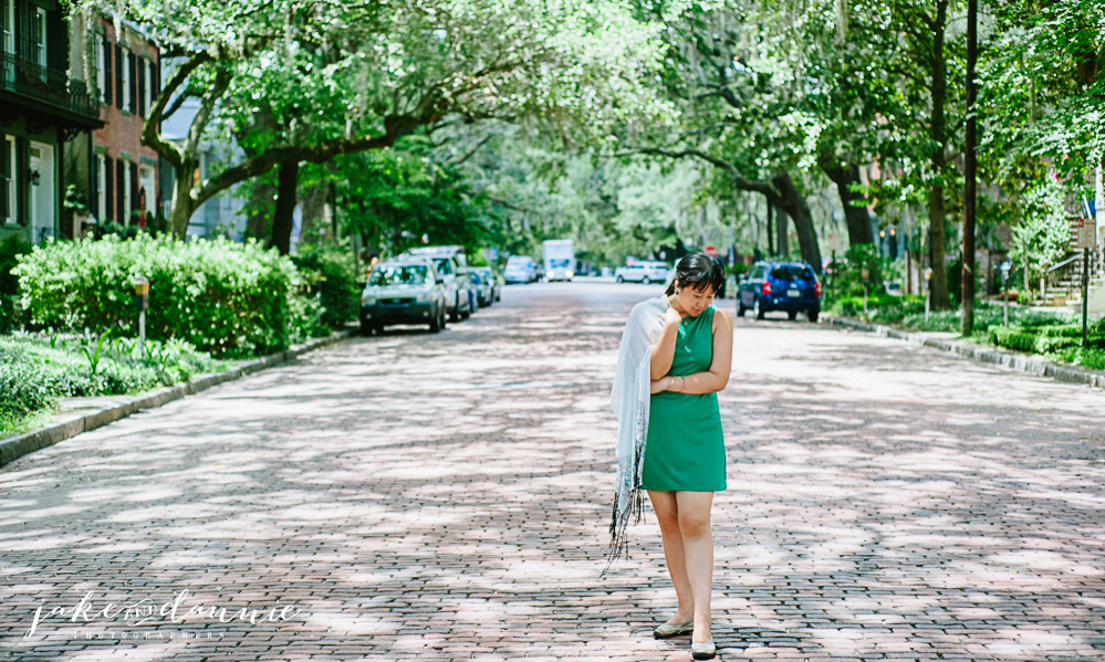 Dannie walks down a shady path and strikes a fashion photography pose in Forsyth Park