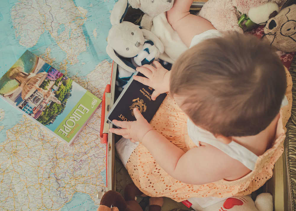Lisa admiring baby's first passport while sitting in a suitcase on top of a map.