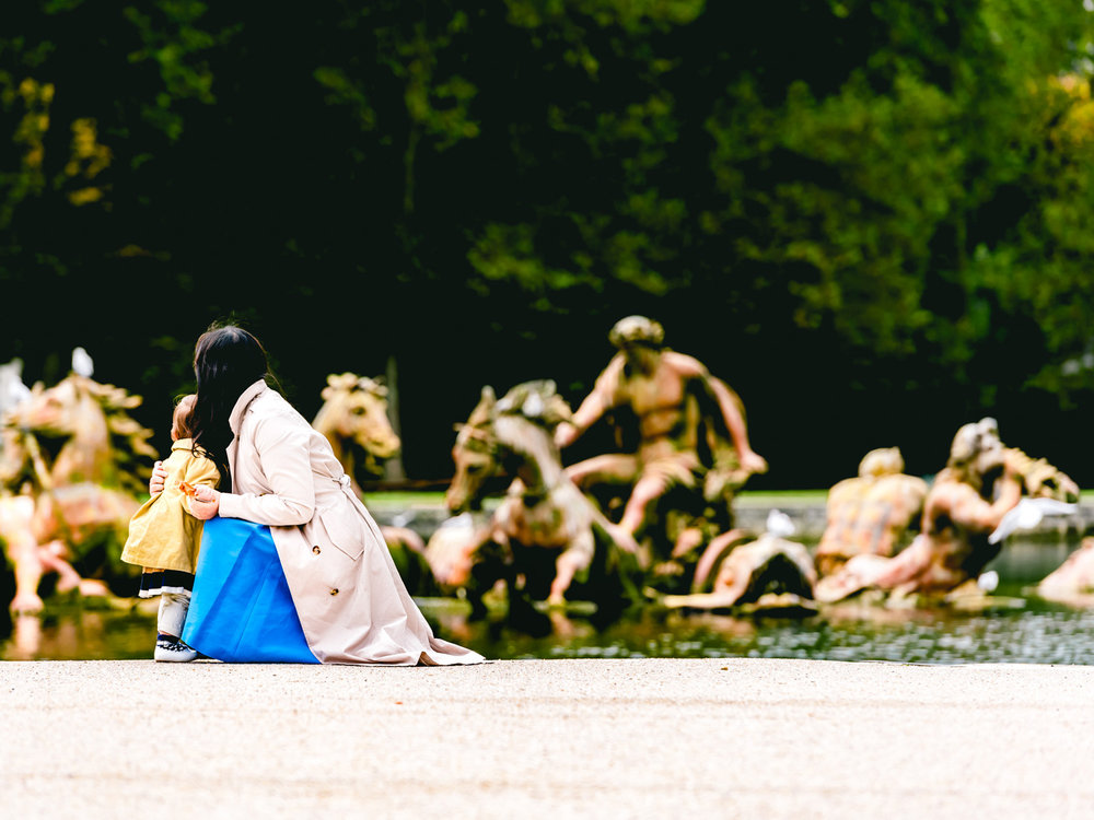 Famous statues in a pool in the versailles gardens.