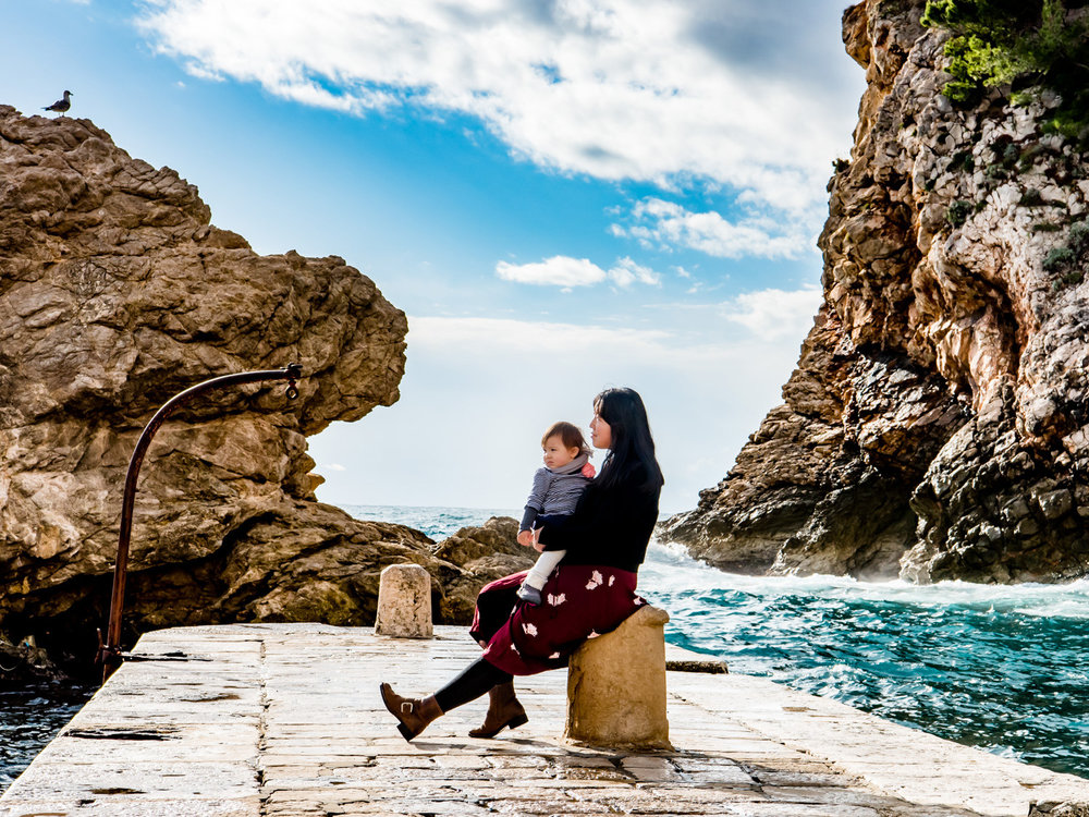 Sitting on the pier near the cliffs by Dubrovnik Croatia.