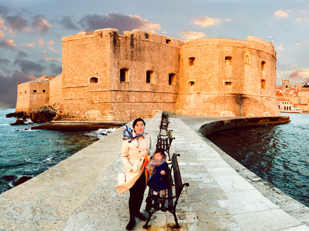 On the pier in Dubrovnik Croatia with the city walls in the background and the old town harbor on the right.