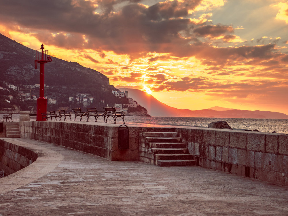 The sun rises over the pier by the Dubrovnik harbor.