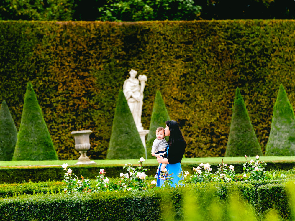 walking by flowers hedges and statues in the versailles gardens.