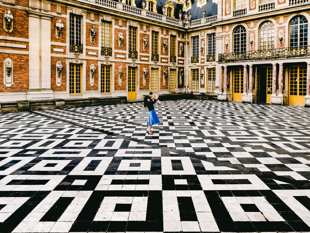 In the courtyard outside the palace of versailles, standing on a giant checkered floor.