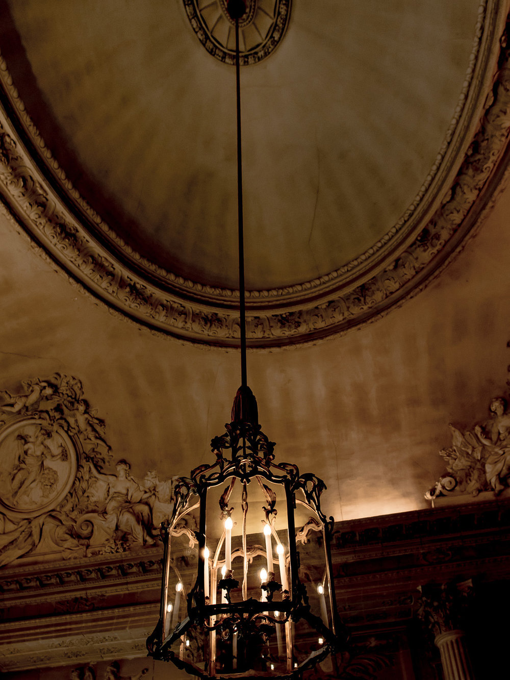 a lantern hangs from an ornate ceiling in the palace of versailles.