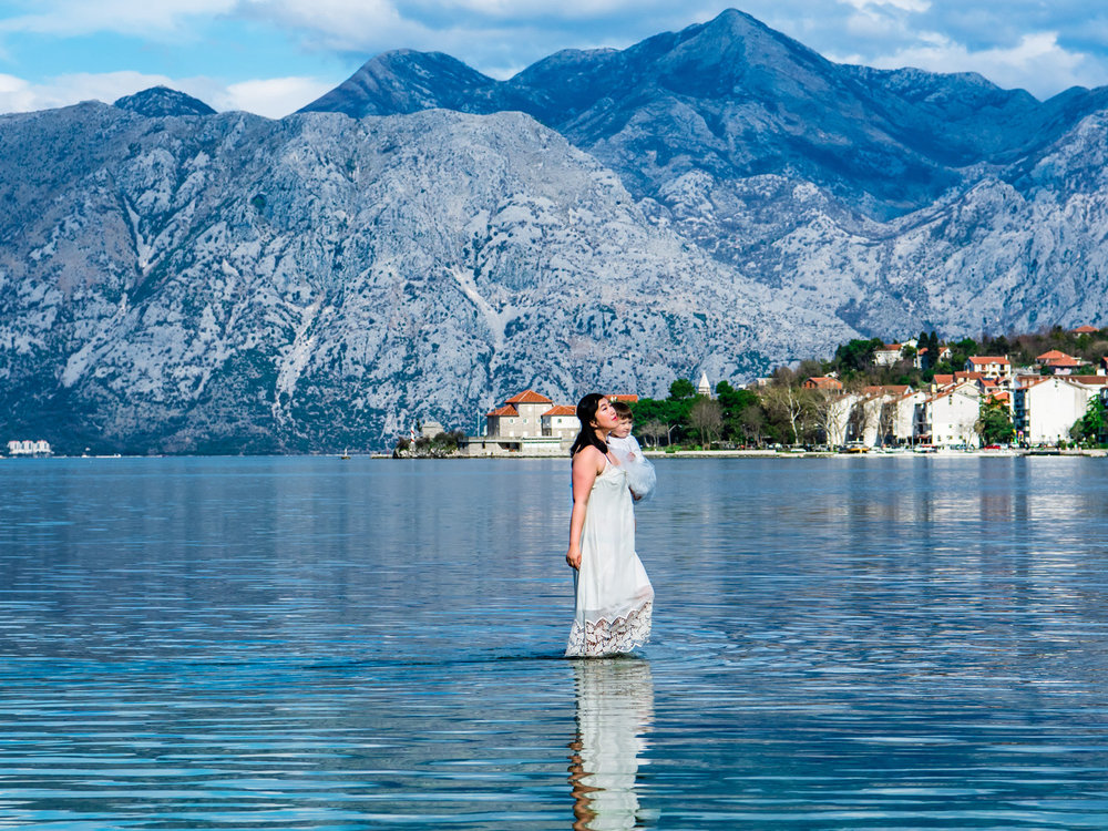Dannie walking on water in Montenegro, with the blue mountains surrounding the Bay of Kotor.