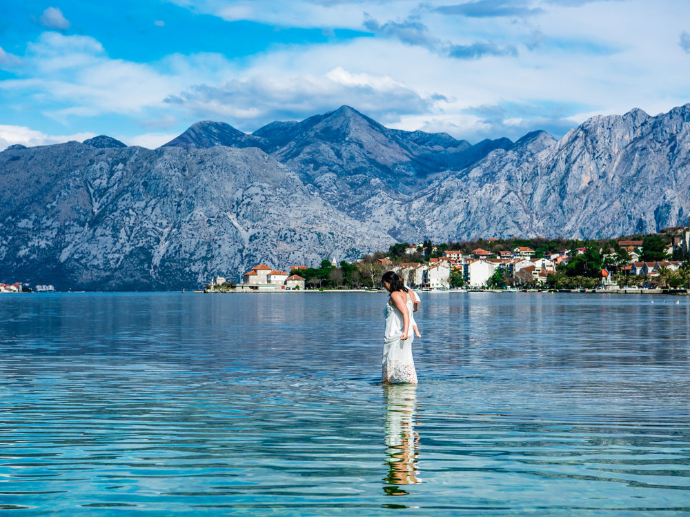 The blue water and mountains in the Bay of Kotor, with Dannie walking on water.