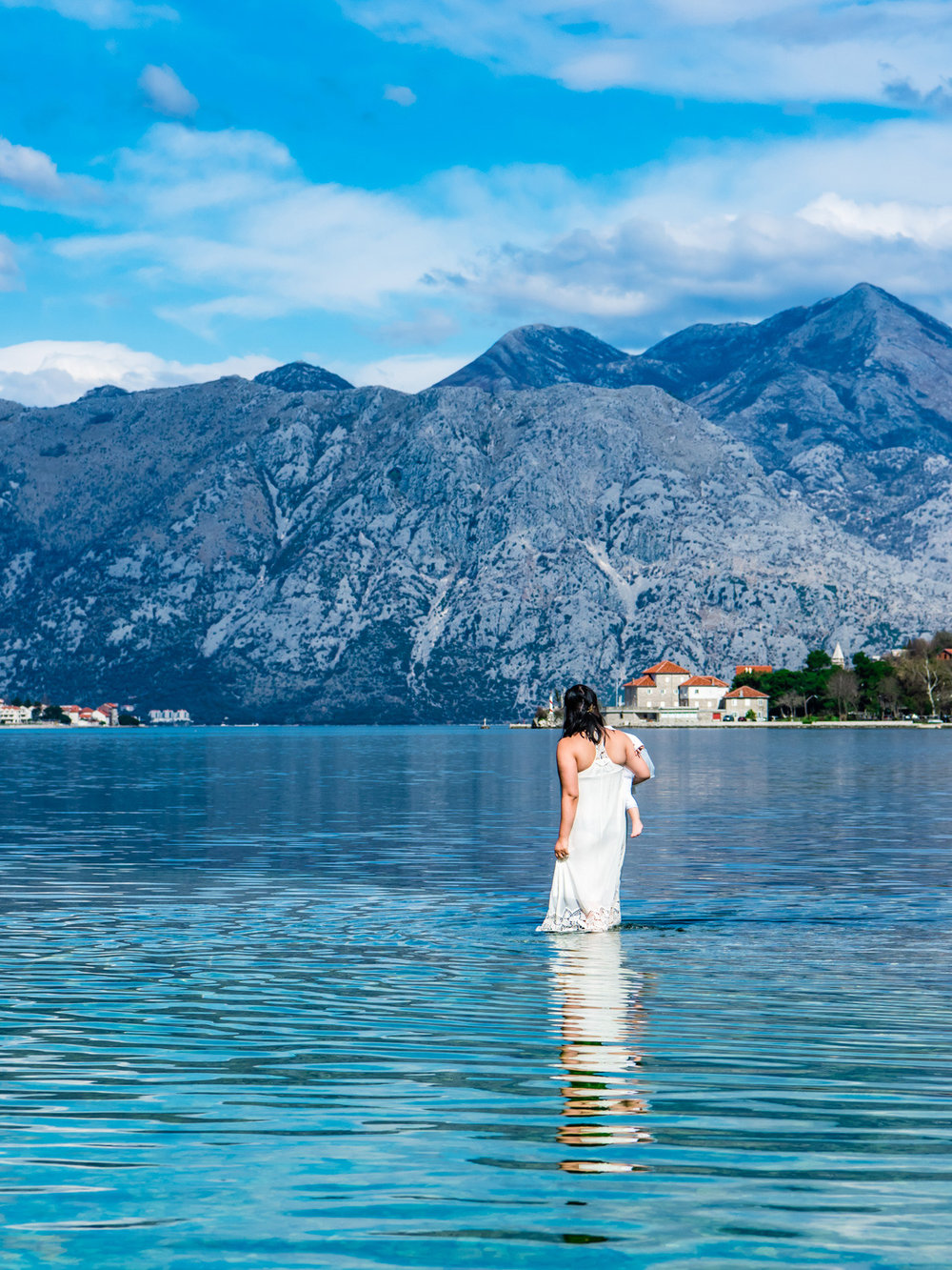 Walking out into the blue water of the Bay of Kotor in Montenegro.