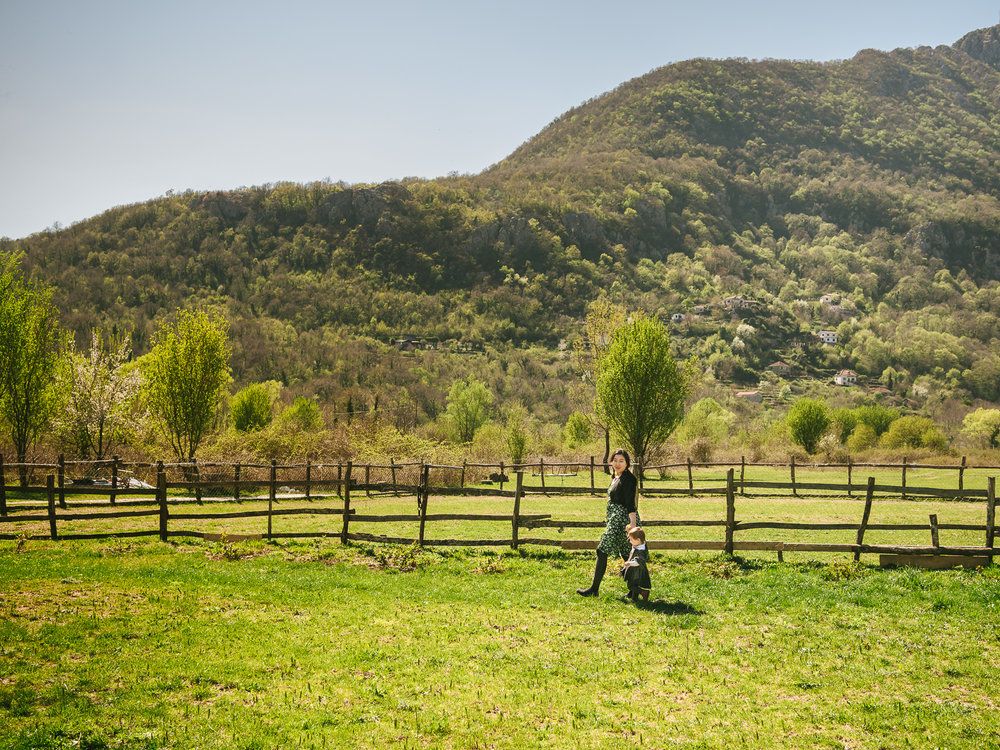 Walking along a wooden fence at the OK Corral Farmstay in Montenegro.