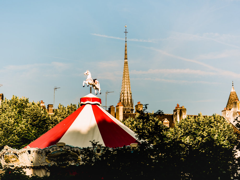 The view over the main square in Beaune, France. A carousel roof rises above the treetops.