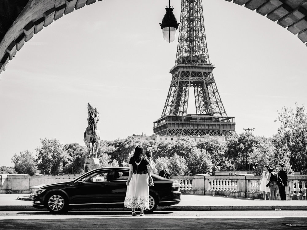 A black and white photo of Dannie and Lisa looking at the Eiffel Tower from the Bir Hakeim bridge.