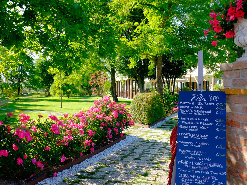 A relaxing restaurant garden on the island of Torcello. A good day trip for travelers visiting Venice, Italy.
