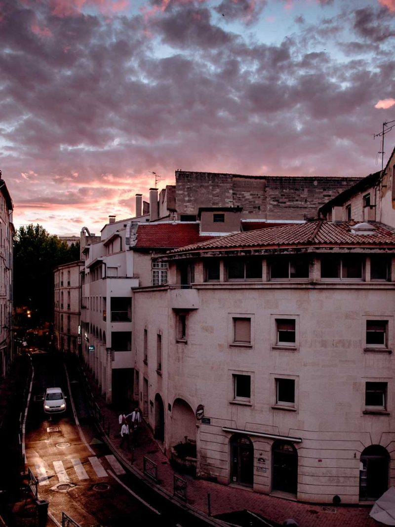 A car drives down the dark streets of Avignon on a summer evening in the south of France.