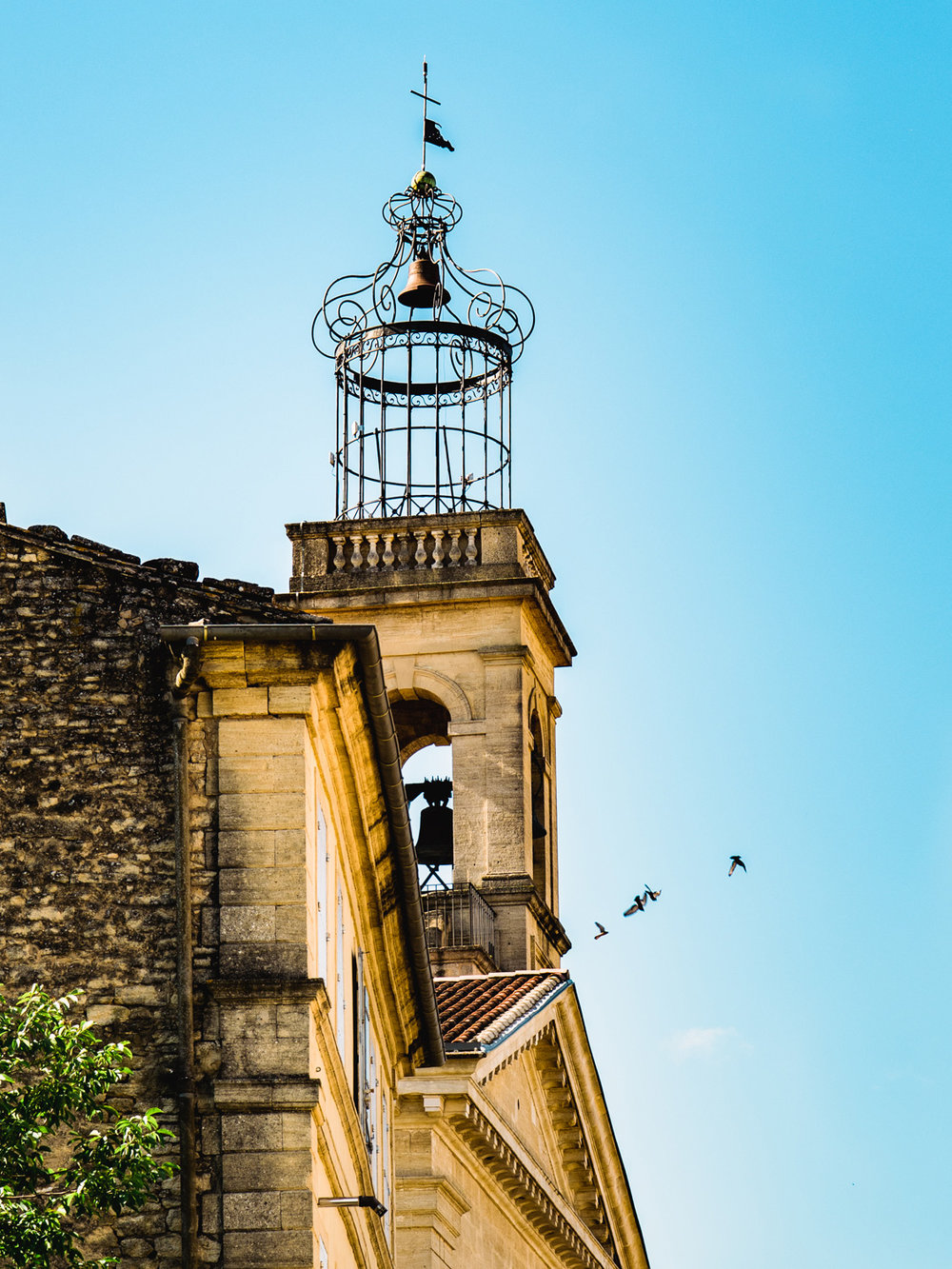 a closeup of the Vers-Pont Du Gard birdcage steeple with some birds flying by for irony.