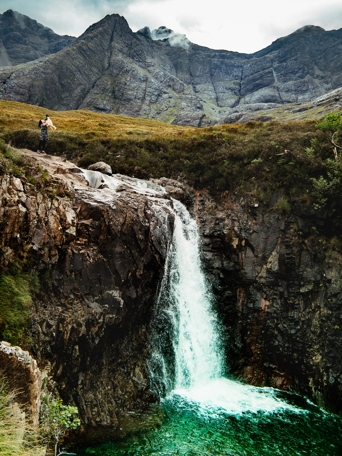 Dannie and Lisa standing over the highest waterfall at the fairy pools on the isle of Skye