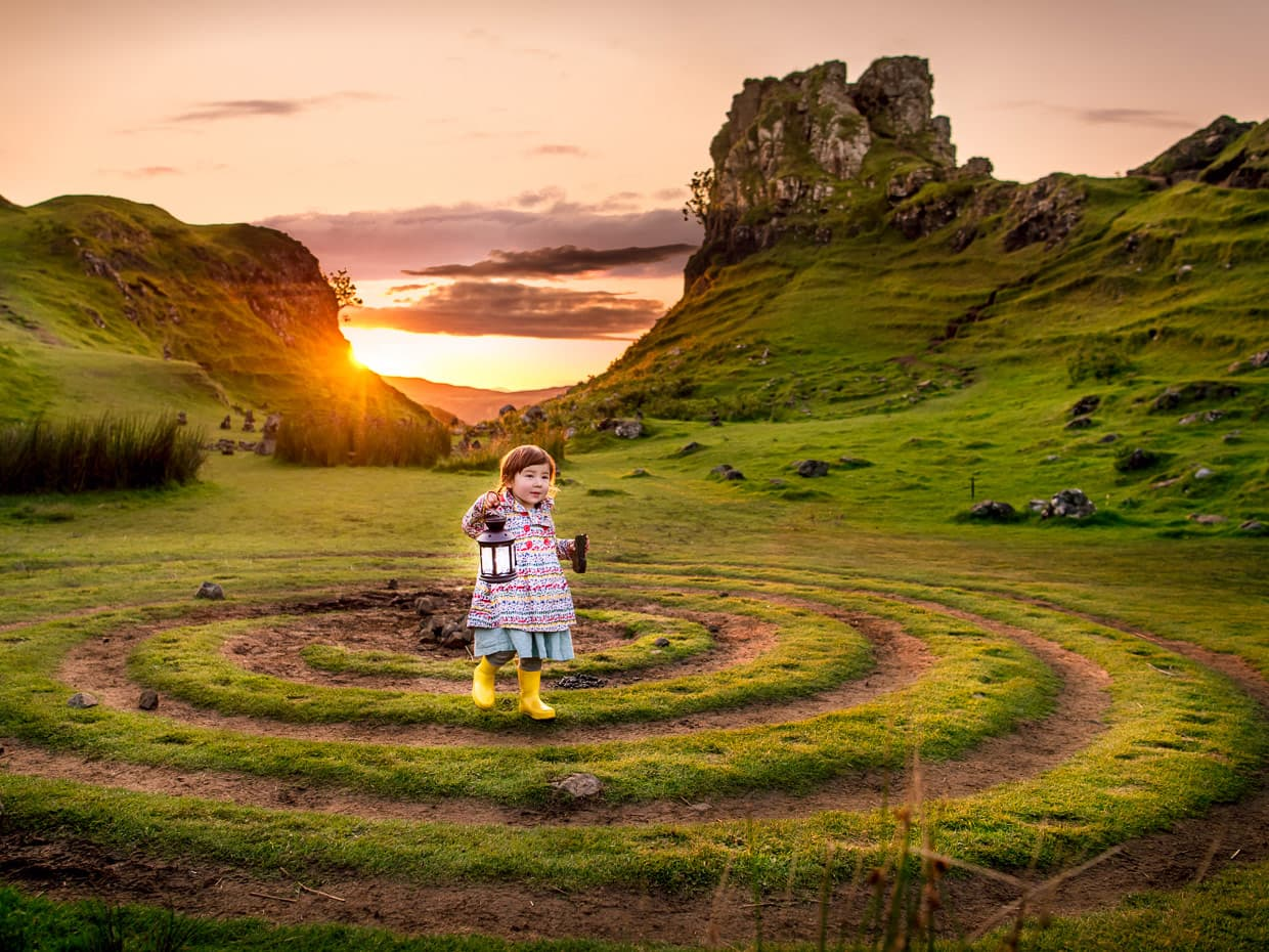 On Scotland's isle of Skye, holding a lantern in a fairy circle at fairy glen.
