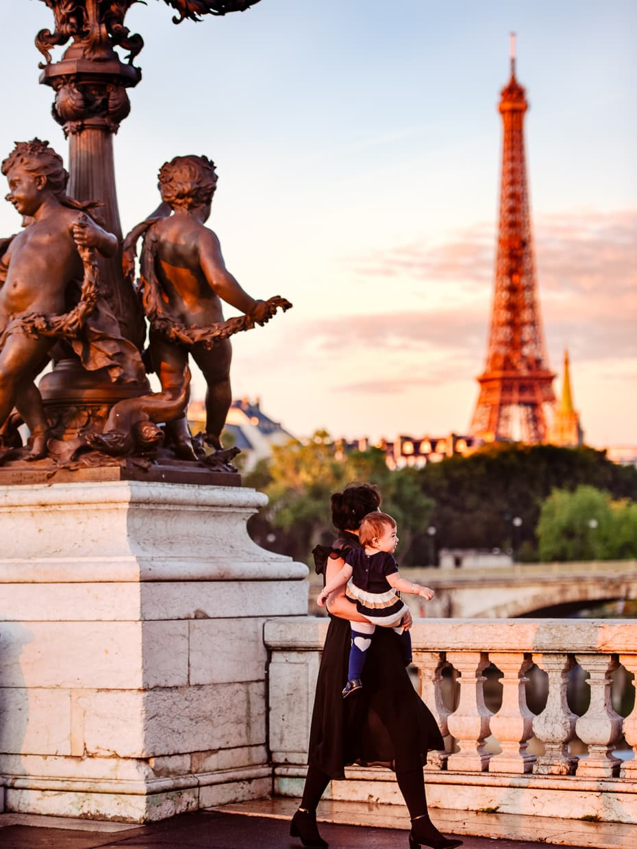 Looking at the Paris sunrise behind the Eiffel Tower while standing on pont Alexandre III
