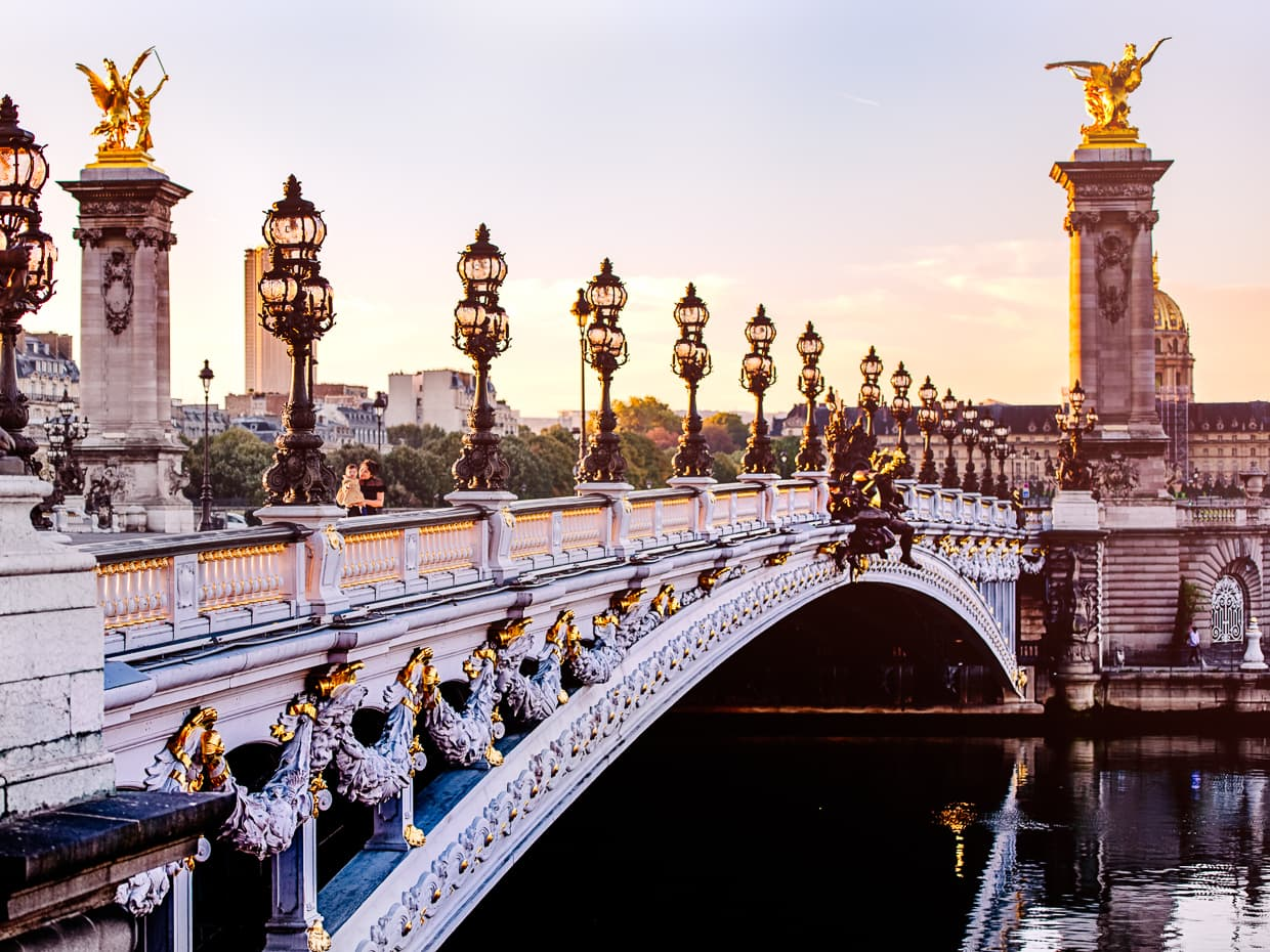 The sun rises over the lampposts of pont Alexandre III in Paris.