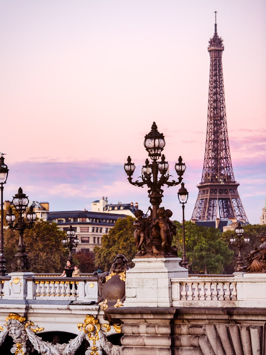 Looking out over Paris at sunrise from pont Alexandre III with the Eiffel Tower in the background.