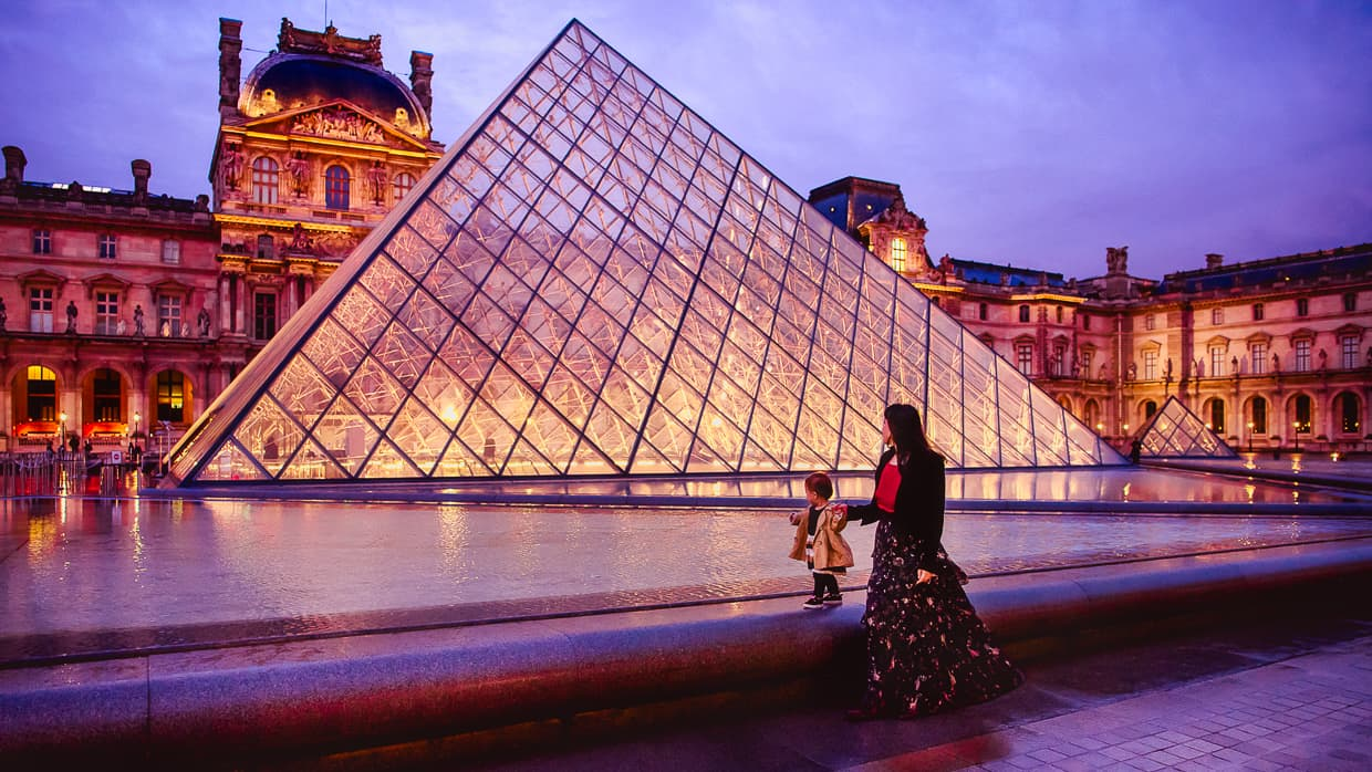 The Louvre pyramids lit up at night.