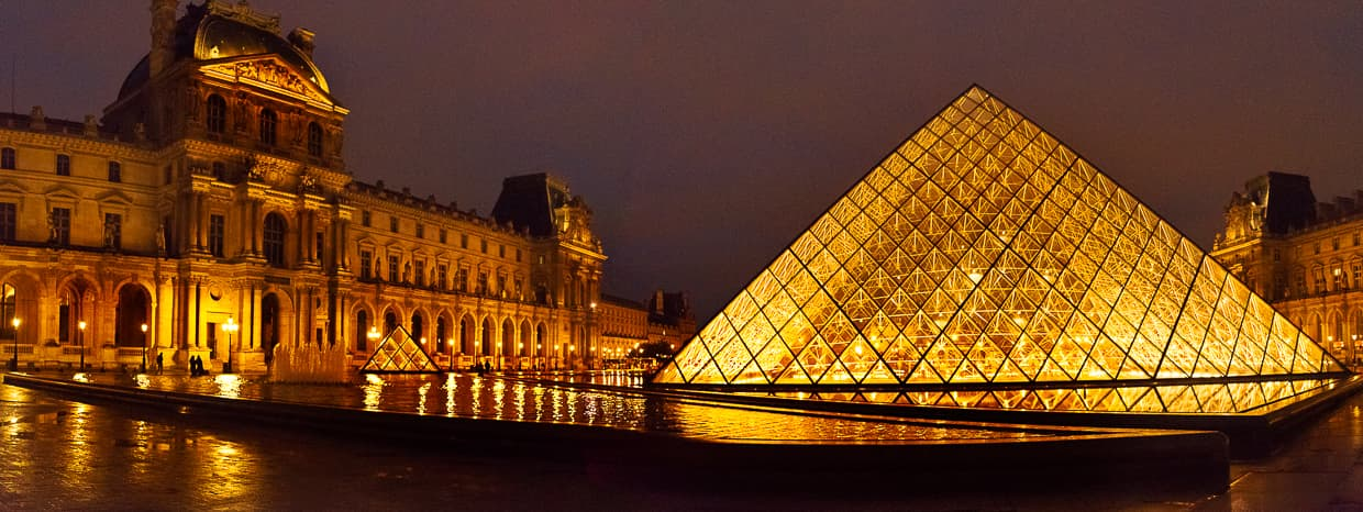 The Louvre courtyard with the pyramid lit up at night.