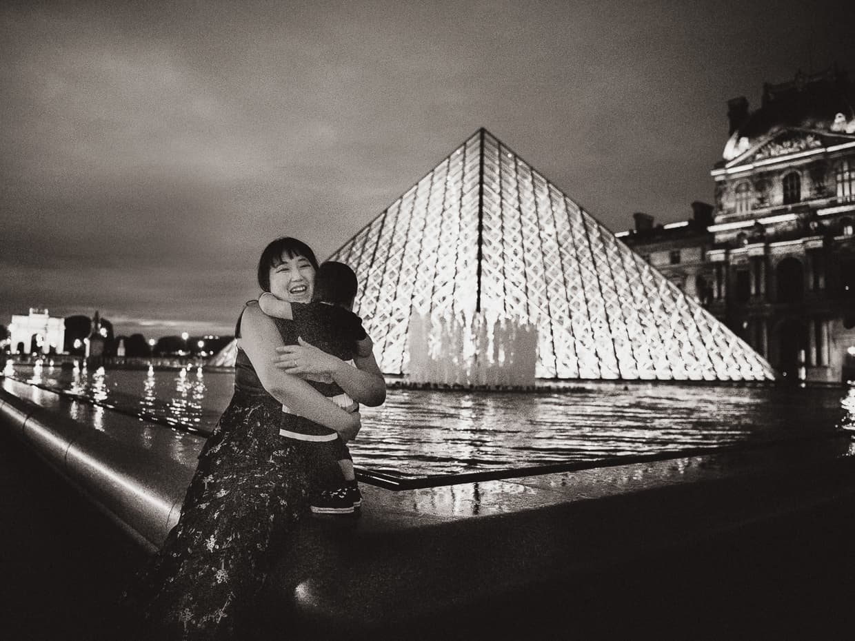 A big hug in front of the illuminated Louvre pyramids under a cloudy fall sky.