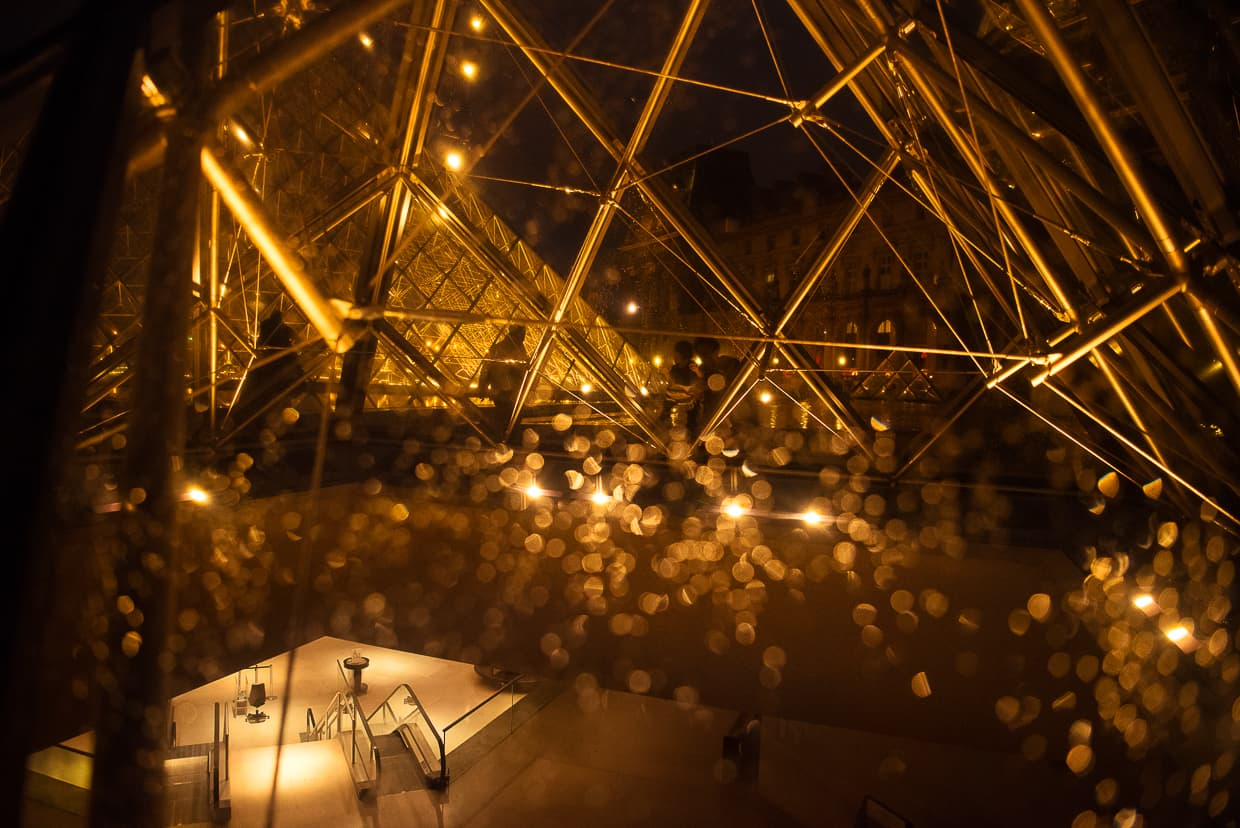 Through the glass of the Louvre pyramid on a rainy night,