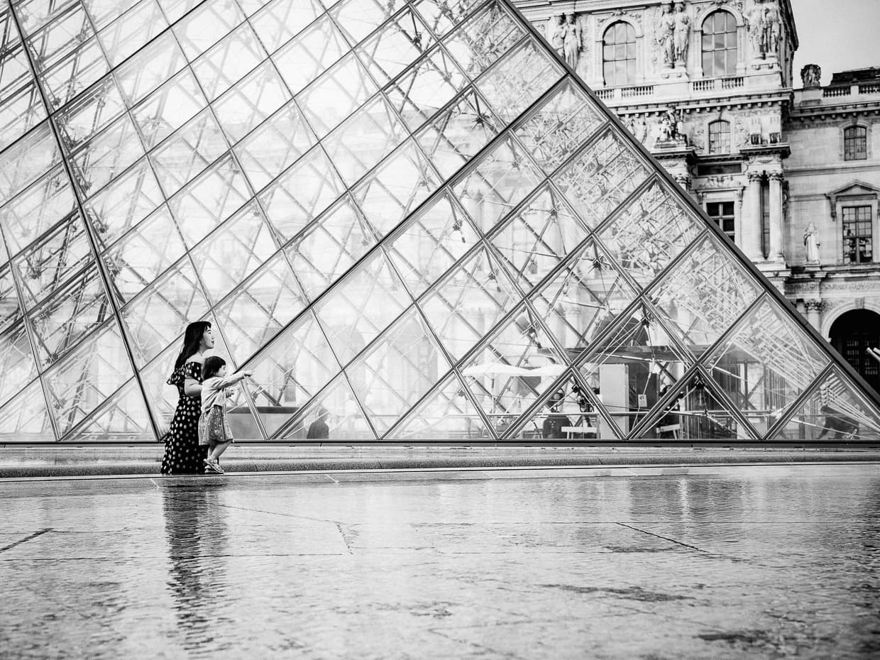walking in front of the Louvre pyramid on a spring morning. Black and white.