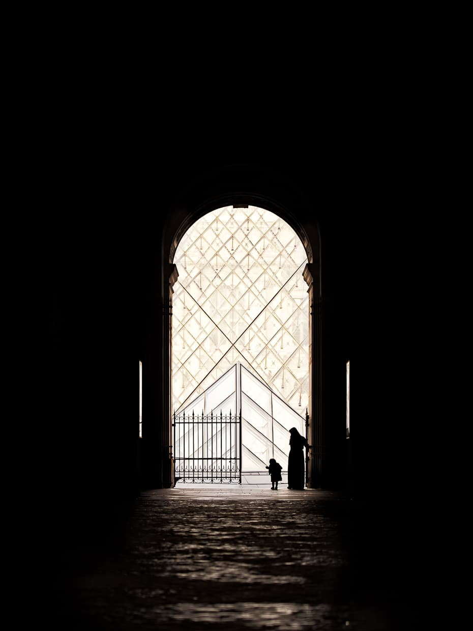A silhouette in under the archway in front of the Louvre pyramid in Paris.
