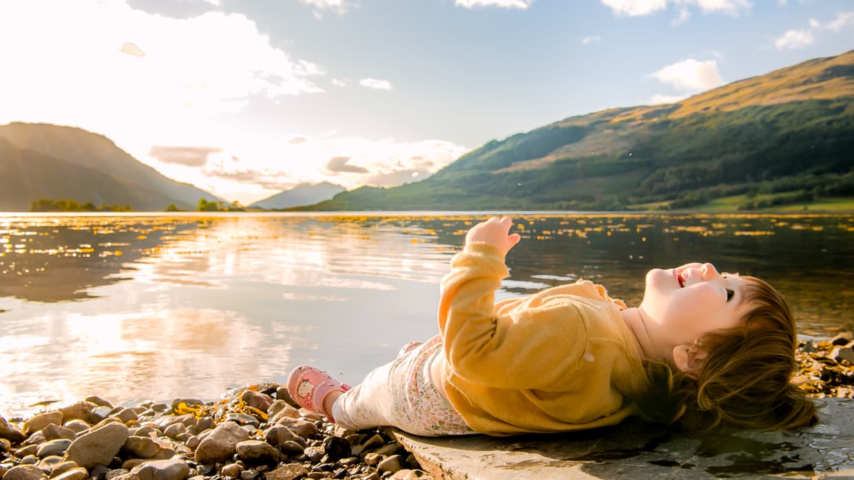 Toddler lying on the beach of loch Leven in Glencoe Scotland