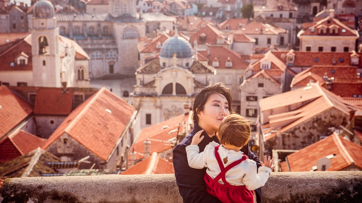 Holding Lisa on the city walls of Dubrovnik with the rooftops and cathedrals in the background.