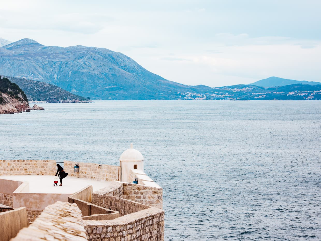 exploring the Dubrovnik, Croatia city walls with the Adriatic Sea as a backdrop.