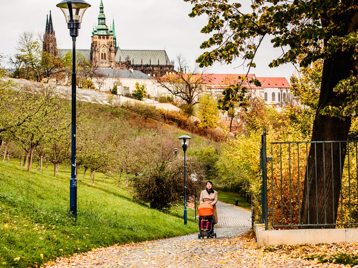 Strolling in Petrin Park with the Prague Castle and St. Vitus Cathedral in the background.