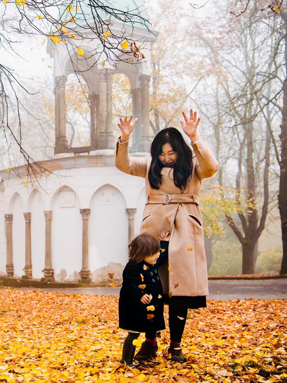 Playing in the colorful fall leaves on a foggy Prague morning in Petrin Park.