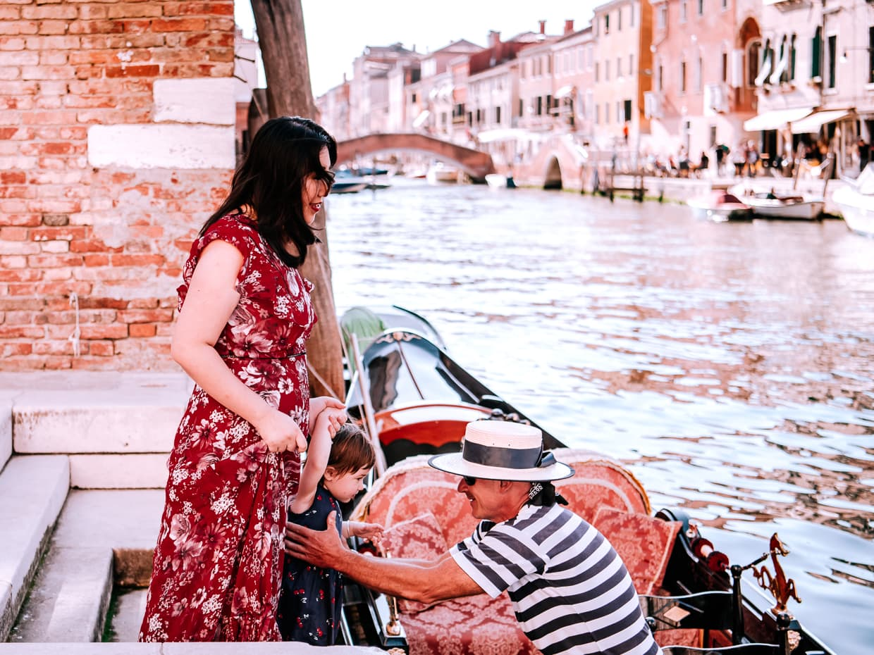A gondolier helping mother and child into a gondola in Venice, Italy.