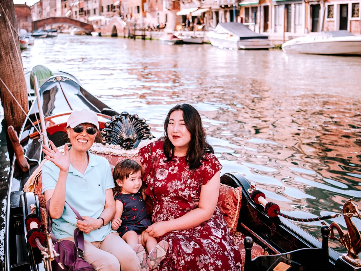 Three generations sitting in a Venice gondola.