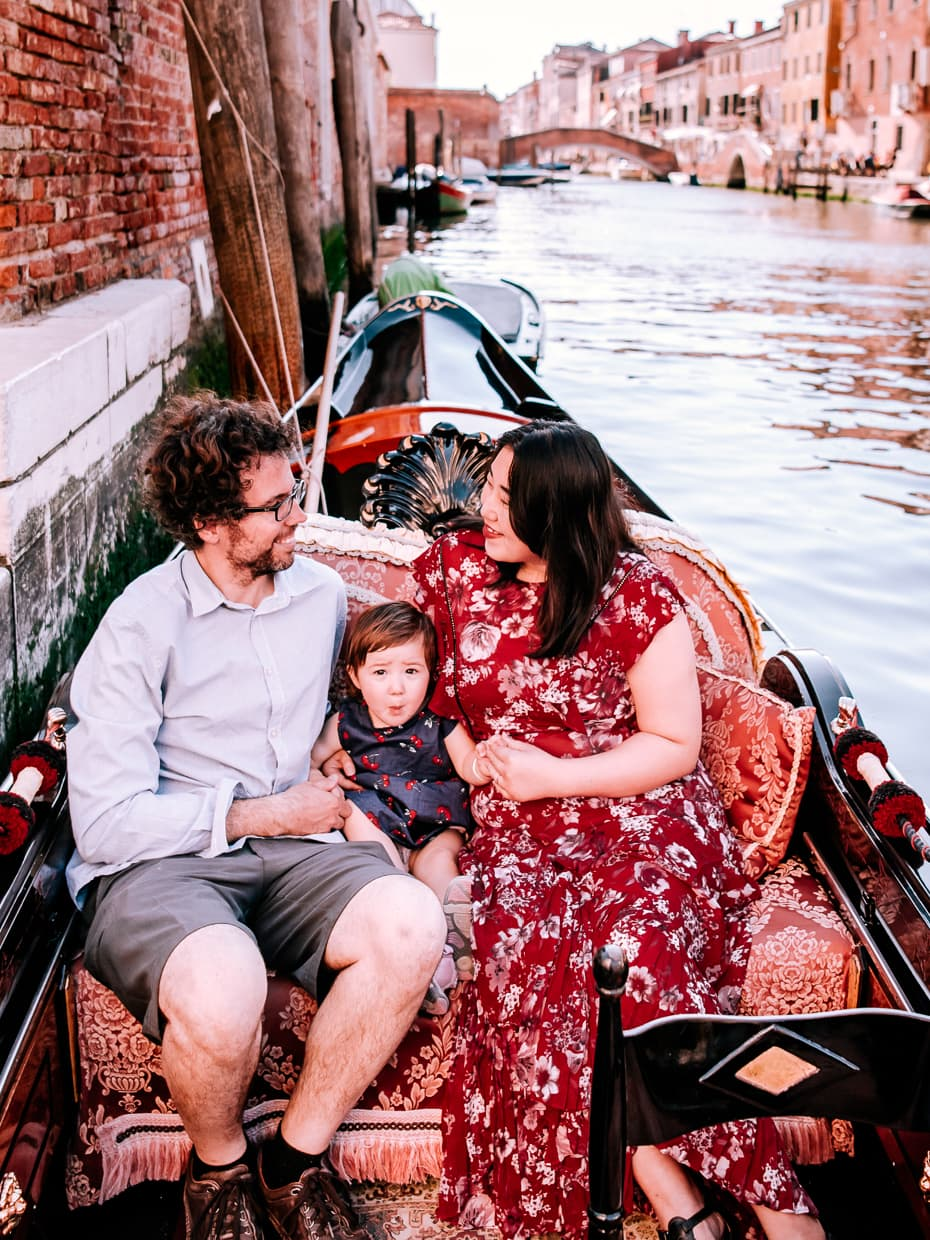 Man woman and child sitting in a gondola in Venice.