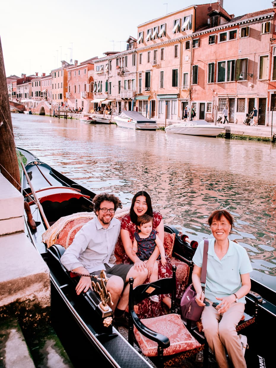 Four people getting ready for a gondola ride in Venice, Italy.,