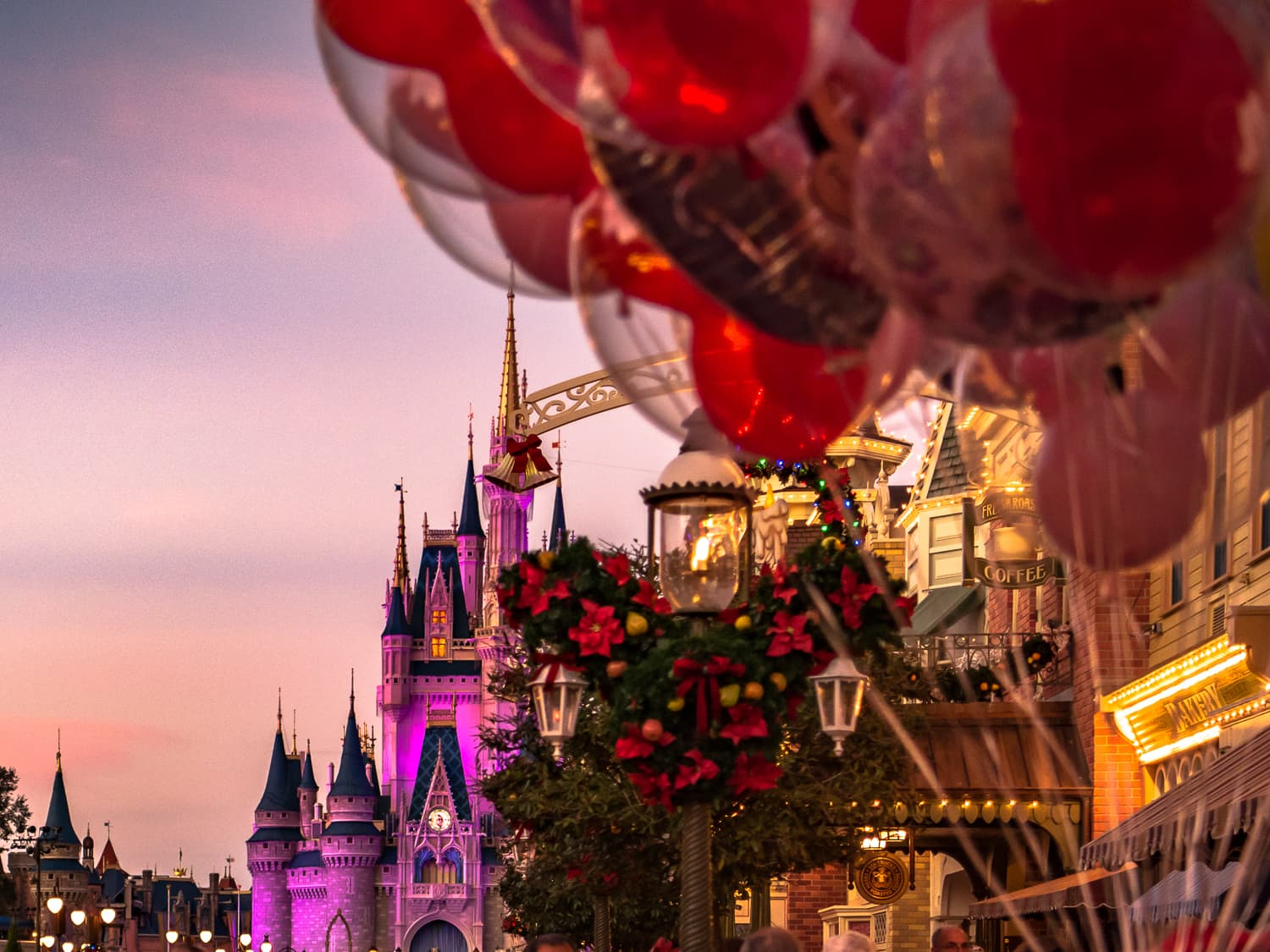 Ballons and Christmas decorations in front of the cinderella castle at magic kingdom.