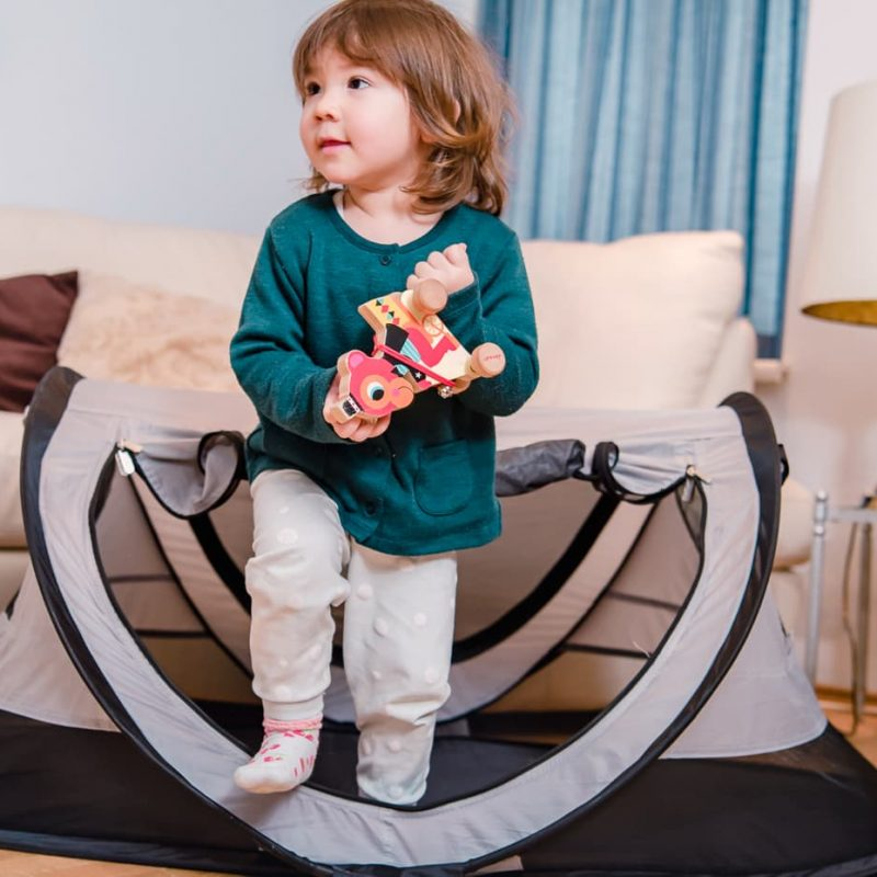 Toddler playing outside her Kidco Peapod Plus Baby Travel Tent.